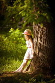 Girl stands near a tree in sunlight — Stock Photo