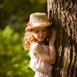 Little girl in straw hat standing near a tree — Stock Photo #48335551