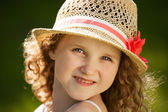 Little happy curly girl in a hat — Stock Photo