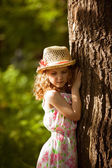 Little girl in straw hat standing near a tree — Stock Photo