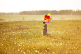 Young happy woman with balloons in a field — Stock Photo
