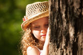 Girl with hat standing near the tree in thought — Stock Photo