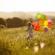 Happy little girl running across the field — Stock Photo