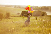 Happy young woman with balloons among a field — Stock Photo
