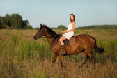 Girl in white dress on a horse — Stock Photo