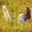 Happy woman lying in a field of grass and flowers — Stock Photo #51134411