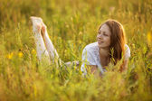 Happy woman lying in a field of grass and flowers — Stock Photo