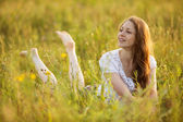 Young happy woman looks out of grass — Stock Photo