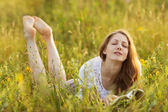 Happy girl with a book in the grass dreaming — Stock Photo