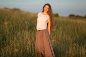Beautiful long-haired woman in a skirt and white blouse — Stock Photo