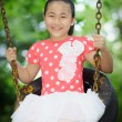 Foto Stock: Little girl playing on swing