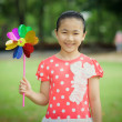 Stock Photo: Little girl playing pinwheel