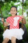 Little girl playing on the swing — Stock Photo
