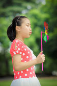Little girl playing pinwheel — Stock Photo