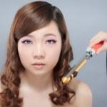 Beautiful asian woman curling hair — Stock Photo