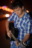 Lonely young artist playing guitar — Stock Photo