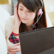 Stock Photo: Young asiwomenjoying music with laptop