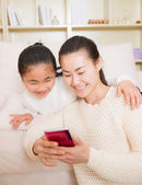 Mother and daughter using smart phone — Stock Photo