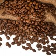 Coffee beans spilling out of rustic bag onto white - Stock Photo