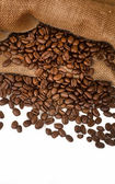 Coffee beans spilling out of rustic bag onto white — Stock Photo