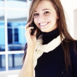 Young woman talking on cell phone smiling — Stock Photo