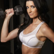 Smiling fitness woman looking into mirror lifting weights. - Stock Photo