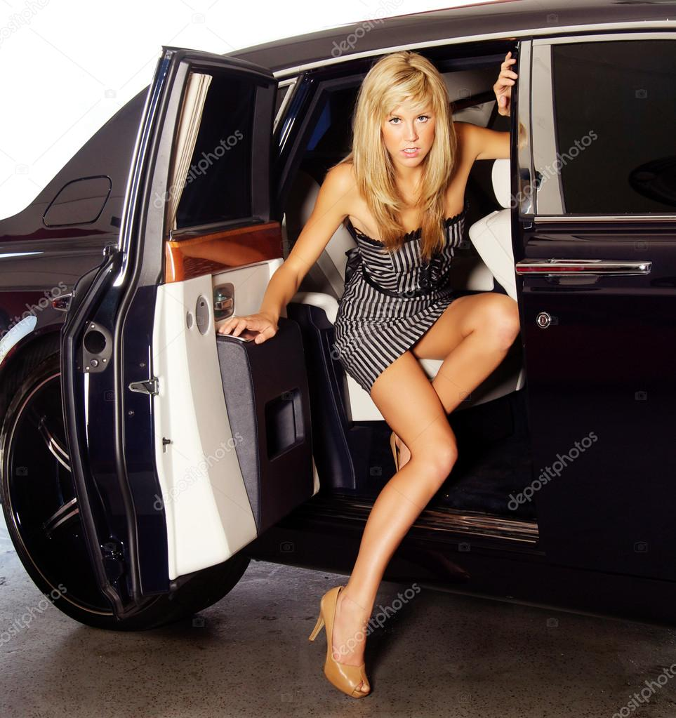 Beautiful Young Woman Exiting A Luxury Car Stock Photo