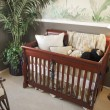 Cherry wood baby crib in nursery interior. - Stock Photo