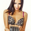 Beautiful young woman holding remote control — Stock Photo