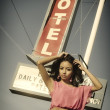Beautiful young woman posing beside classic American road sign for Motel on Route 66 — Stock Photo #26209627