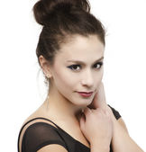 Beautiful young woman's face with hair in bun — Stock Photo