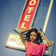 Beautiful young woman posing beside classic American road sign for Motel on Route 66 — Stock Photo #26582747