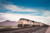 Freight train traveling through desert — Stock Photo
