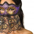 Beautiful mysterious woman's face behind ornate purple and gold mask — Stock Photo