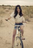 Young woman fashion portrait on beach bike — Stock Photo