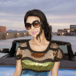 Beautiful young woman standing beside convertible car — Stock Photo