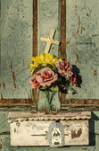 Rustic old weathered and worn doorway with charming display of flowers and cross — Zdjęcie stockowe