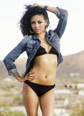 Beautiful young woman wearing bikini and denim jacket — Stock Photo