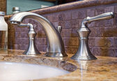 Modern faucet tap and granite counter — Stockfoto