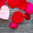Candle and rose petals — Stock Photo