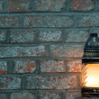 Stock Photo: Candle on brick background with text space