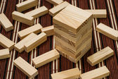 Wooden blocks tower and block spread around — Stock Photo