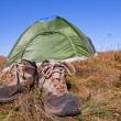 Pair of touristic boots near a tent — Stock Photo