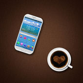 Mobile phone and coffe cup on a brown — Stock Photo
