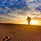 Hiker walk by a sandy desert — Stock Photo