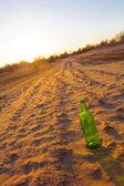 бутылка на песке на вечер — Стоковое фото
