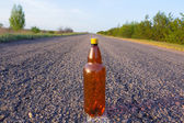 Bottle on an asphalt road — Stock Photo