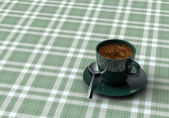 Cup coffee on table with tablecloth — Stock Photo