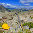 Climbing tools helmet and ice axe  in a mountains — Stock Photo