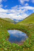 Small lake among green mountains — Stock Photo